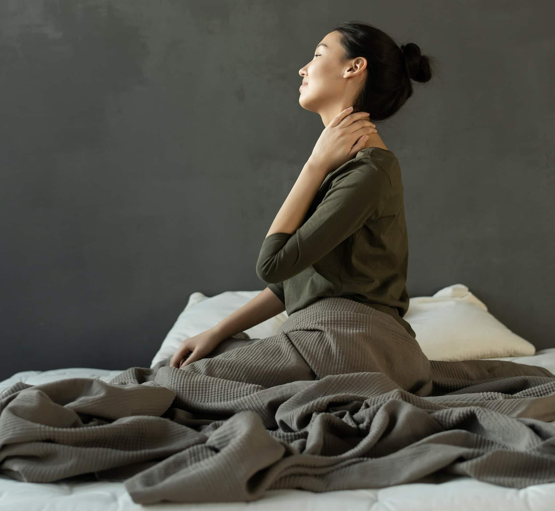 woman-in-gray-dress-sitting-on-bed-3754299